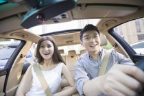 Front view of excited chinese couple riding in car — Stock Photo