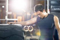 Chinese man leaning on large tire in crossfit gym and looking down — Stock Photo