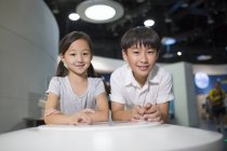 Chinese children sitting at table in museum — Stock Photo