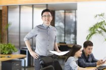 Chinese male IT worker standing with papers in office — Stock Photo