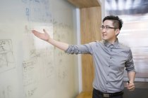 Chinese businessman showing plan on whiteboard — Stock Photo