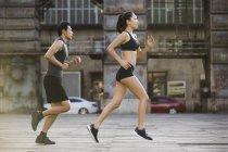 Paar chinesische Jogger laufen auf Straße — Stockfoto