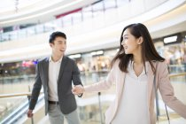 Chinese couple holding hands in shopping mall — Stock Photo