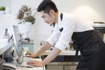 Proprietario del caffè cinese utilizzando il computer — Foto stock
