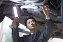 Китайский автомеханик осматривает автомобиль с фонариком — стоковое фото