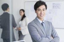 Китайский бизнесмен, стоящий со сложенными руками — стоковое фото