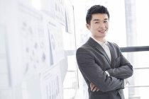 Uomo d'affari cinese in piedi con le braccia incrociate alla lavagna bianca — Foto stock