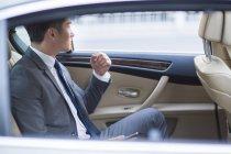 Homme d'affaires chinois assis sur le siège arrière de voiture — Photo de stock