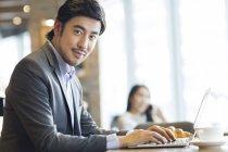 Chinesischer Geschäftsmann mit Laptop im Café sitzen — Stockfoto