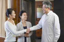 Chinese doctor shaking hands with patients in hospital hall — Stock Photo