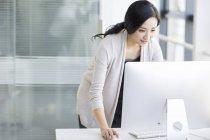 Femme chinoise permanent et utilisez l'ordinateur dans le Bureau — Photo de stock