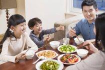 Familia China juntos cenando en la mesa - foto de stock