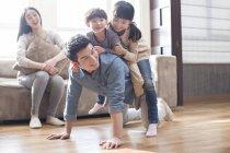 Crianças chinesas, jogando com o pai no chão enquanto a mãe rindo no sofá — Fotografia de Stock