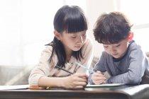 Fille chinoise aider frère étudie à table — Photo de stock