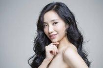 Chinesische Frau posiert mit Hand am Kinn — Stockfoto