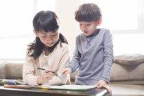 Китайские сестра, помогая брата, обучение на дому — стоковое фото
