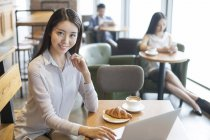 Chinese businesswoman sitting with laptop in cafe — Stock Photo