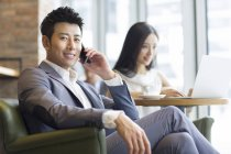Chinese man talking on phone with woman sitting in background with laptop — Stock Photo