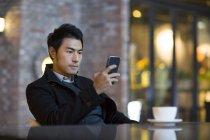 Uomo cinese utilizzando smartphone al caffè della città — Foto stock