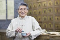Senior Chinese man holding cup of tea — Stock Photo