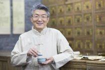 Uomo anziani cinese che tiene tazza di tè — Foto stock
