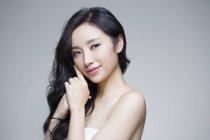 Portrait of beautiful chinese woman touching hair — Stock Photo
