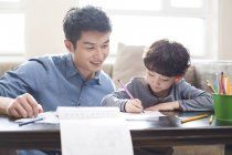Chinese father smiling and helping son with homework — Stock Photo
