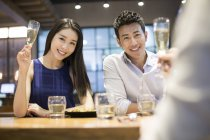 Chinese friends cheering with champagne in restaurant — Stock Photo
