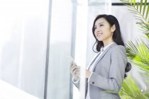 Chinese businesswoman holding smartphone in office building — Stock Photo