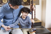 Chinese father teaching son traditional musical instrument erhu — Stock Photo