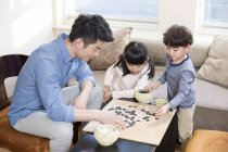 Chinese children playing the game of Go with father — Stock Photo