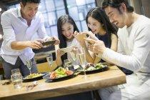 Amis chinois prenait des photos de nourriture dans le restaurant — Photo de stock