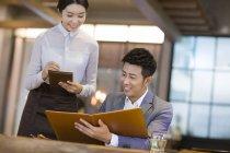 Hombre chino de ordenar en el restaurante con la camarera - foto de stock