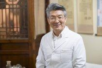 Старший китайський лікар, стоячи в клініку і дивлячись в камери — стокове фото