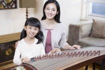 Chinos madre e hija con cítara instrumento musical tradicional - foto de stock
