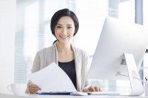Femme chinoise assis avec des papiers au bureau et à la recherche à huis clos — Photo de stock