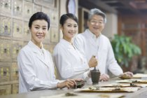 Chinese doctors posing in traditional pharmacy — Stock Photo