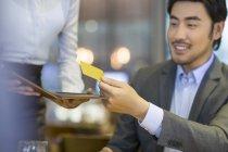 Chinese man giving waitress credit card — Stock Photo