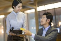 Chinese man paying by credit card in restaurant — Stock Photo