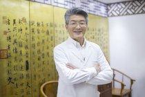 Médico chinês sênior em pé com os braços dobrados — Fotografia de Stock