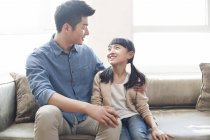 Chinês-pai e filha sentada no sofá — Fotografia de Stock