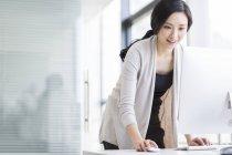 Femme chinoise debout et en utilisant l'ordinateur dans le bureau — Photo de stock