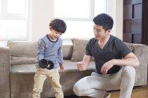 Китайский отец и сын тренируются дома с гантелями — стоковое фото