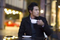 Chinese man drinking coffee at street cafe — Stock Photo