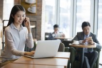 Chinese woman talking on phone and using laptop in cafe — Stock Photo
