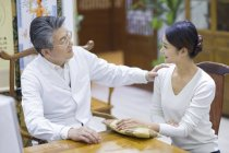 Senior Chinese doctor talking with female patient — Stock Photo