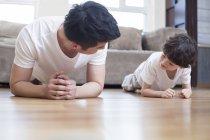Chino padre e hijo practicando tablón plantean en casa - foto de stock