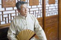 Старший китаец держит винтажный ручной вентилятор в традиционном интерьере — стоковое фото