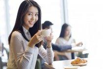 Chinesische Frau posiert mit Kaffeetasse im café — Stockfoto