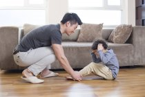 Chinese father helping son exercising at home — Stock Photo